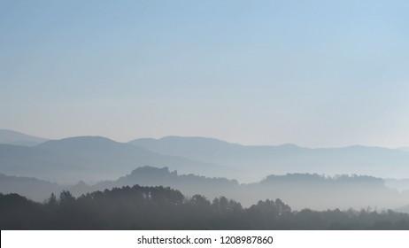 Wooded Lunigiana hills, north Tuscany, Italy. Beautiful misty early morning, calm landscape.