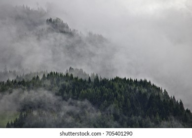 Wooded mountain ridges in the Austrian Alps party obscured by mist and clouds