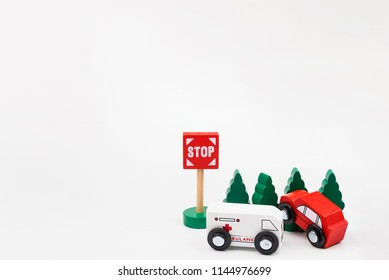 Wooded toy car are crashed. Accident road traffic with wooden toy cars in the town on white background, safety and traffic regulations concept, backgrounds.Transportation system concept