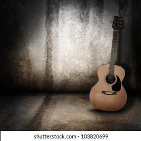 An wooden acoustic guitar is against a grunge textured wall. The room is dark with a spotlight for your copyspace. Use it for a music or concert concept.