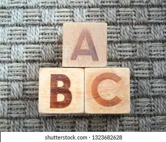 Wooden alphabet blocks spelling abc on grey carpet. Educational toys for children in preschool and kindergarten.