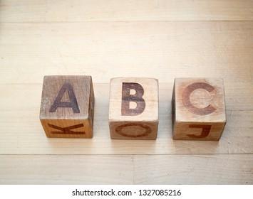 Wooden alphabet blocks spelling abc on hardwood floor. Educational toys for children in preschool and kindergarten.