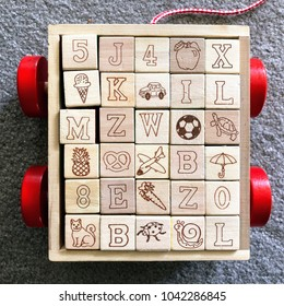 Wooden children's alphabet and emoji blocks in toy cart: 5 J 4 🍎 X 🍦 K 🚗 I L M Z W ⚽ 🐢 🍍 🥨 ✈️ B ☂️ 8 E 🥕 Z 0 🐈 B 🐞 🐌 L