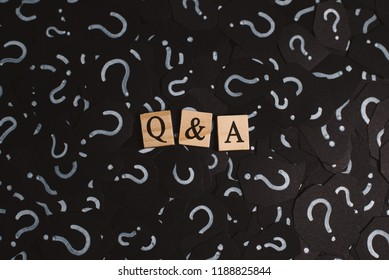 wooden alphabet tiles with Q&A letter on black paper with QUESTION MARK. Concept of Question and Answer Q&A online assist