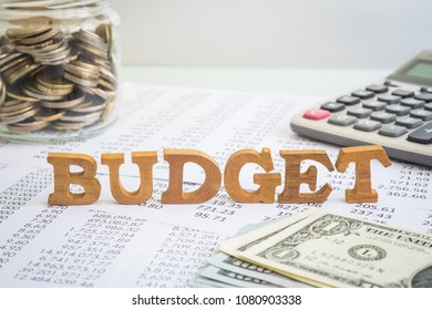 Wooden alphabet word Budget putting on accounting stagement and paperwork with money saving jar, calculator and dollar cash on office table. Concept of financial management and business project.