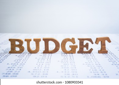 Wooden alphabet word Budget putting on accounting statement and annual summary reports on office table. Blank background and copy space. Financial management and business projects concepts