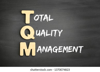 Wooden alphabets building the word TQM - Total Quality Management acronym on blackboard