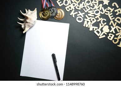 Wooden alphabets, empty white paper and medals