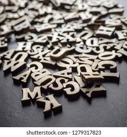Wooden alphabets on a dark woode background, close up
