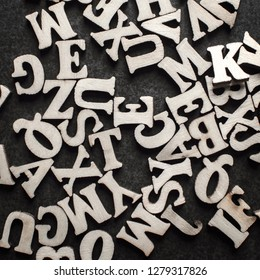 Wooden alphabets on a dark woode background, from above