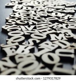 Wooden alphabets on a dark woode background, shallow DOF