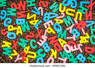 Wooden alphabets over coffee beans background