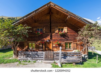 Wooden alpine hut with geraniums in flower boxes on the Eng-Alm on the large Ahornboden in the sunlight, Tirol, Austria