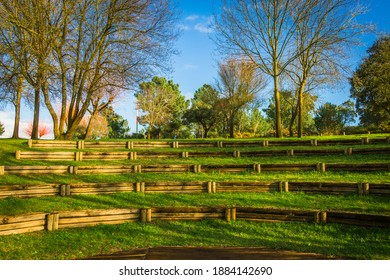 Wooden Amphitheater in the middle of the park, with green vegetation