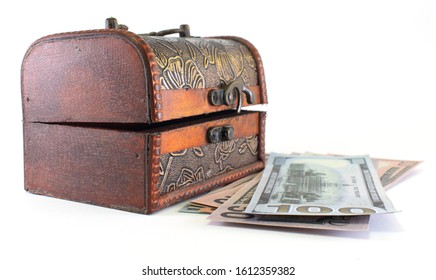 Wooden antique casket with US banknotes close-up.Isolated white background.Business concept