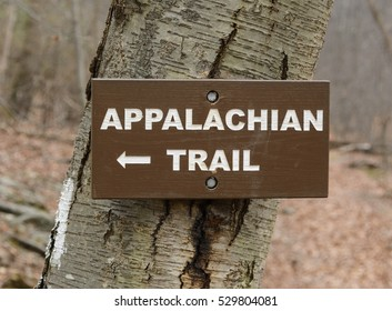A wooden Appalachian Trail sign with white letters on brown painted wood, directing hikers to the Appalachian Trail, Penn Mar, Washington County, Maryland, USA.