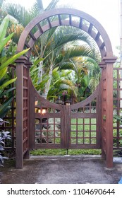 Wooden arbor with close gate in garden. Wooden arched entrance to the backyard