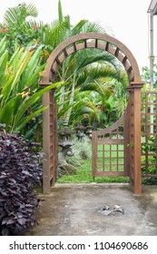 Wooden arbor with close on half gate in garden. Wooden arched entrance to the backyard