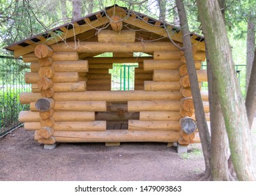 Wooden arbor made of logs with a triangular roof and windows cut into logs. For relaxation and barbecue in the garden.