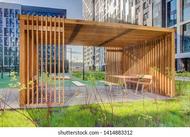 Wooden arbor. Modern wooden gazebo in courtyard of residential complex. Canopy in residential garden. Urban gazebo. rest, relaxation in residential building in summer. Patio subject Moscow may 2019