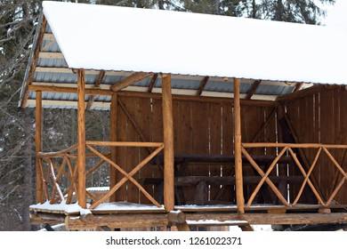Wooden arbor in the winter in the snow. Arbor in the mountains in the snow among the firs. Wooden canopy among the snowdrifts in a frosty sunny day.