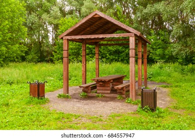 Wooden arbour in park with table, benches and two garbage cans on the sides a background of green trees (summer)