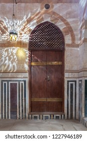 Wooden arched door on stone wall decorated with marble panels and lantern shadows on the wall, Old Cairo, Egypt