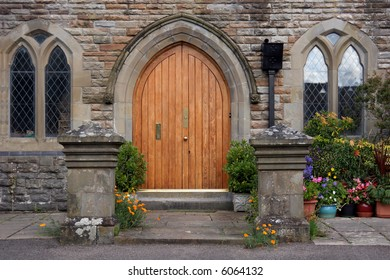 Wooden arched doorway of a converted church with gothic style windows set into stone walls. Flowers and shrubs at the entrance and to the side.
