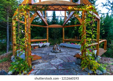 Wooden arched structure with a firepit at its center and vines crawling, with various colors of silk lantern boats displayed and flower petals scattered on the floor all around.