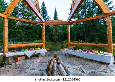 Wooden arched structure with a firepit at its center, with various colors of silk lantern boats displayed on the surrounding benches - Wide angle picture taken outside in northern Quebec