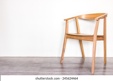wooden armchair on gray tile floor and warm background