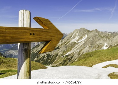 Wooden arrow points to summit group in the Alps.