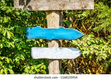 Wooden arrow sign with arrows in colors pointing in the right directions