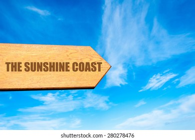 Wooden arrow sign pointing destination THE SUNSHINE COAST, AUSTRALIA  against clear blue sky with copy space available. Travel destination concept  image