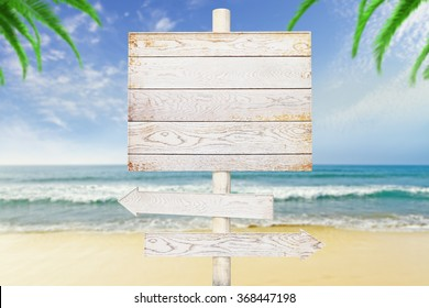 Wooden arrow signs on beach background