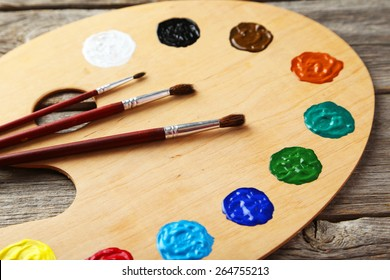 Wooden art palette with paints on grey wooden background