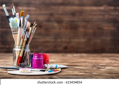 Wooden art palette with tubes of oil paints and a brush. Art and craft tools. Artist's brush, canvas, palette knife. Space for text. Items for children's creativity.Acrylic paint and brushes.