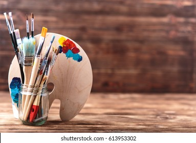 Wooden art palette with tubes of oil paints and a brush. Art and craft tools. Artist's brush, canvas, palette knife. Space for text. Items for children's creativity.Acrylic paint and brushes