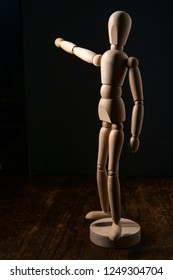 Wooden articulated artist doll pointing towards copy space