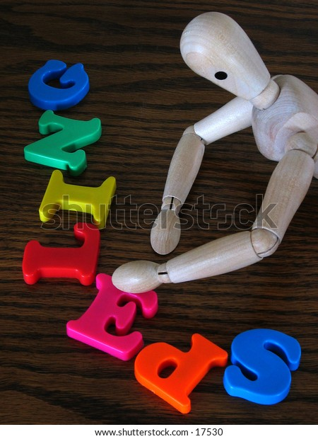 A wooden artist's dummy playing with some cheap plastic letters.