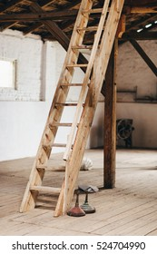 Wooden attic ladder stairs in a rustic interior.