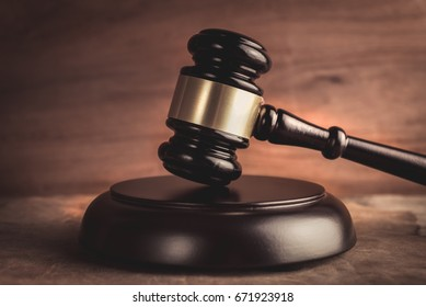 Wooden auctioneer or judges gavel for dispensing justice or knocking down sale prices against a background with light and shadow