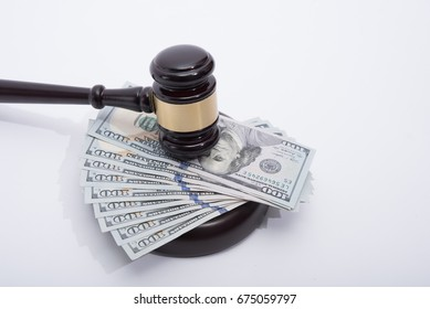 Wooden auctioneer or judges gavel for dispensing justice or knocking down sale prices  on pile of US dollars against white background
