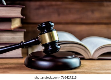 Wooden auctioneer or judges gavel for dispensing justice or knocking down sale prices against a background with light and shadow, vintage style