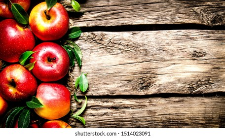 Wooden background with big red fresh apples