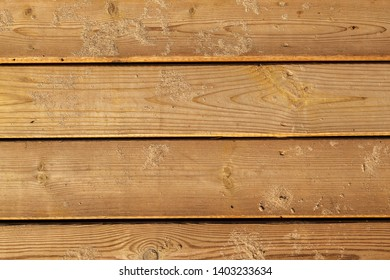 Wooden background. Boards in sand. Wooden path on the sandy beach. Weathered wooden boardwalk on the sand. Use of natural materials. Wood surface texture