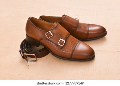 Wooden background with brown man shoes with belt