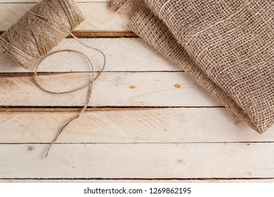 Wooden background with canvas and coarse thread with space for text.