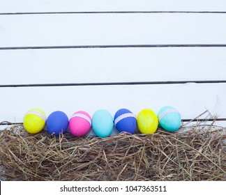 Wooden background with easter eggs painted in vibrant colors