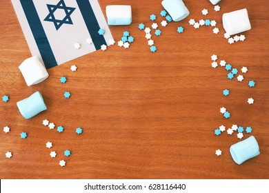 Wooden background framed by marshmallows, candies and a flag for Israeli independence day